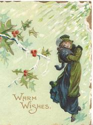WARM WISHES in gilt below berried holly, woman in old style winter dress walks front in blizzard