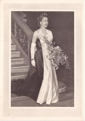 Queen Elizabeth II at staircase bottom holding large bouquet