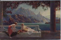 two ladies lounging by lake with mountains in distance