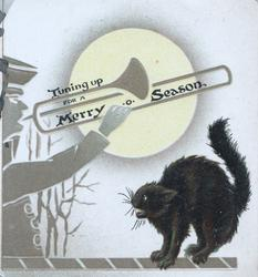 TUNING UP FOR A MERRY CHRISTMAS. trumpet player tunes up under a moon, bristled black cat protests