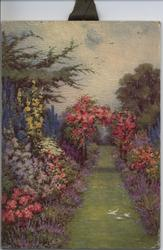 grass path with garden on either side and a pink flowered arbor over the path