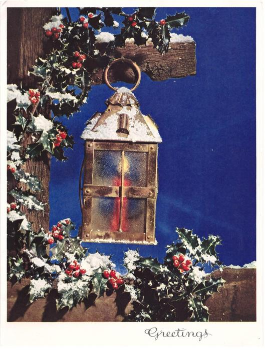GREETINGS snow dusted, holly trimmed wooden post holds lantern, blue background