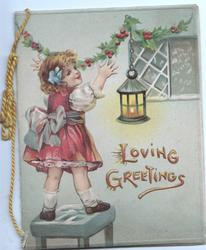 LOVING GREETINGS in gilt, girl hangs holly, lantern hangs by window. olive green backgrouind