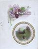 GREETINGS in white on small grey plaque below violets above gilt bordered circular rural inset