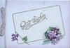 GOOD WISHES on white plaque, bunch of violets below, pale purple background