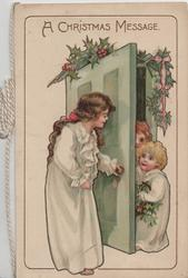 A CHRISTMAS MESSAGE mother in nightgown opens door to 2 girls, holly above