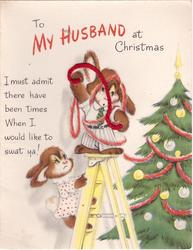 TO MY HUSBAND AT CHRISTMAS rabbits decorate Xmas tree, 1 stands on ladder tangled in red yarn
