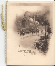 LADEN WITH GOOD WISHES men riding camels past building