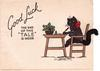 "GOOD LUCK THE END OF THIS ""TALE"" IS INSIDE black cat sits at writing desk with pipe cleaner tail, bowl of holly,"