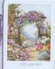 EVERY GOOD WISH below garden inset, many highly coloured flowers, purple wisteria on wooden arch