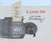 A LUCKY DIP in red, ON YOUR BIRTHDAY! placard pops up out of barrel with good options black cat sits looking front