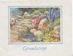 GREETINGS in green below garden of many flowers & delphiniums, rocks and stone steps