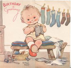 BIRTHDAY GREETINGS in red,girl sits with finger through hole in sock, socks on line