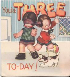 YOU'RE THREE TO-DAY two children & dog inside house, girl on left blind-folded, dog front