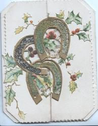 no front title, 3 gilt glittered perforated horseshoes across both front flaps in front of berried holly