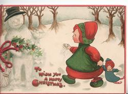 TO WISH YOU A HAPPY CHRISTMAS in red, snowman holding holly winces having been snowballed by girl holding doll