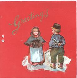 GREETINGS in gilt over boy & girl standing facing each other, red background