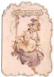 GLAD GREETINGS above woman in old style dress sits on swing, ornamental die-cut border