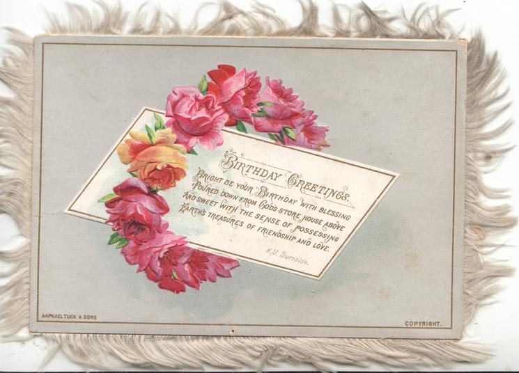 BIRTHDAY GREETINGS verse on white plaque circled by wreath of red roses, white fringes