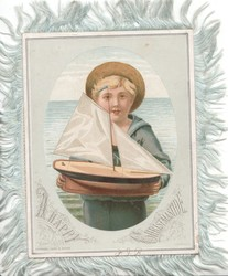 A HAPPY CHRISTMASTIDE inset of boy holding model boat, sea behind
