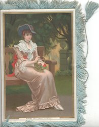 WISHING YOU A MERRY CHRISTMAS below seated woman in silk dress
