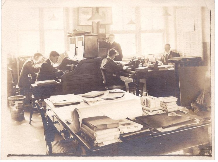 author Grace C. Floyd sitting at her desk, Raphael House editiorial deparment