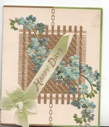 HAPPY DAYS in gilt on pale blue ribbon & bow with forget-me nots on square wicker design