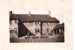 no front title, sepia inset photograph, child stands front of large 2 story manor