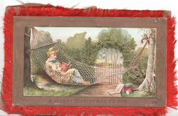 A MERRY CHRISTMAS TO YOU on margin below girl reading in hammock in garden in front of gate in hedge