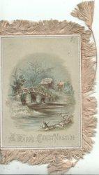 A HAPPY CHRISTMAS TIDE below watery rural winter scene, bridge & cottage across river