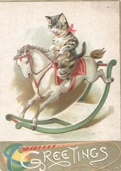 GREETINGS in white on gilt plaque at base with ball & whip, cat rides rocking horse