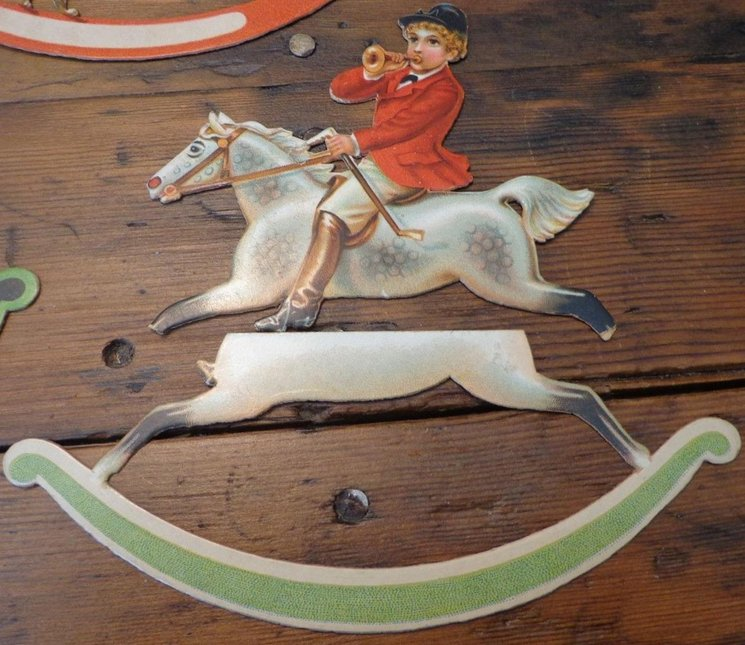 young boy in hunting attire on white rocking horse