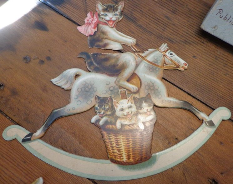 mother cat with pink ribbon rides a white rocking horse, three kittens in basket below her