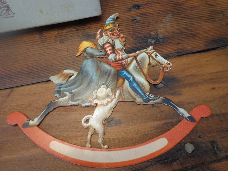Punch character and gowned ?Judy(head missing) ride a white rocking horse with dog below them