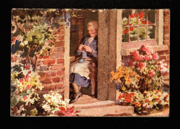 lady knitting within a cottage doorway