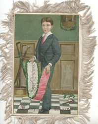 A MERRY CHRISTMAS boy facing standing  facing partly left holding white & pink scarf inscribed HAPPY CHRISTMAS