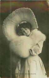 MISS MARIE STUDHOLME, stands facing front, enormous hat & muff, head tilted, looks front