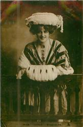 MISS MARIE STUDHOLME standing leaning on wooden railing, large muff, hand-coloured