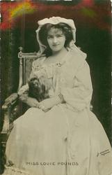 MISS LOUIE POUNDS seated with terrier,