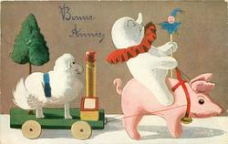 snow clown rides toy pig that is pulling cart with a sheep on it