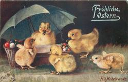 two ducklings under umbrella have many Easter eggs on table, three chicks in front