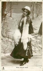 MISS PHYLLIS DARE  snow scene, wearing furs, standing facing left, looking front