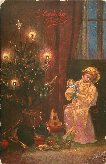 girl sits asleep, cuddling doll, beside lighted Xmas tree