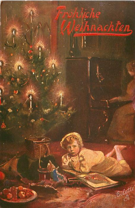 child lies beside lighted Xmas tree