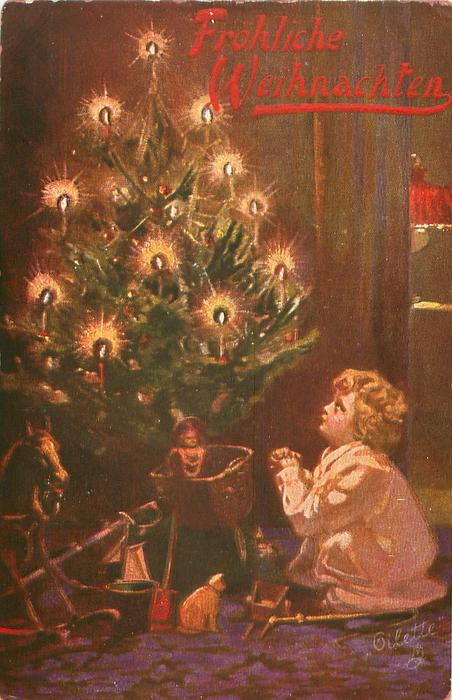 child kneels praying beside lighted Xmas tree