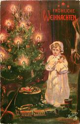 child stands cuddling doll beside lighted christmas tree
