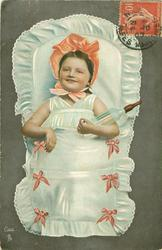 girl decked out as a baby, holding a bottle in her left elbow, tucked into a sleeping pouch