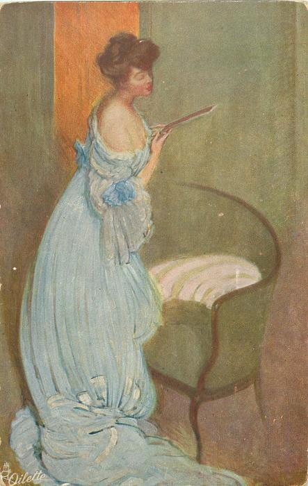 lady in off shoulder long blue dress, stands looking down at thin book, in front of green love seat