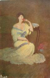 lady in off shoulder long yellow dress trimmed with blue, sits by a table holding red flower to her face
