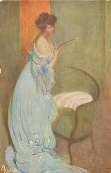 IM BOUDOIR  lady in off shoulder long blue dress, stands looking down at thin book, in front of green love seat